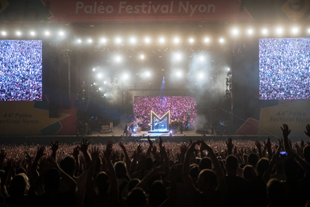 Nyon, Switzerland - 24 July 2019 :  general view on the main stage with crowd of audience at concert of extravagant French singer-songwriter and guitarist Matthieu Chedid called –M- Editorial