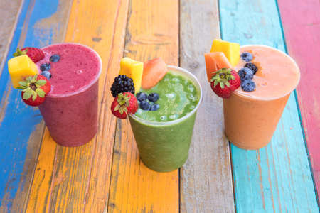 Colorful, tasty and healthy fruit smoothies on a colorful wood table