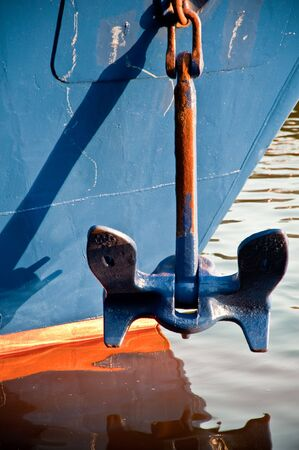 ship anchor:  A metal anchor casting shadow on a ship and from reflection Stock Photo