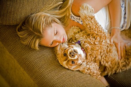 couch: A young female resting with her dog on the couch