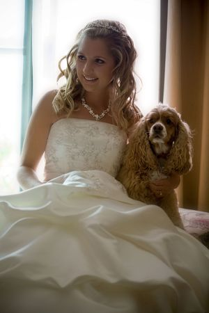 A bride posing with her dog photo
