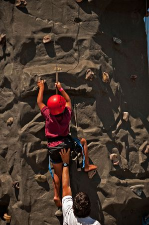 A boy climbing up a rock wall with his father supporting him Stock fotó