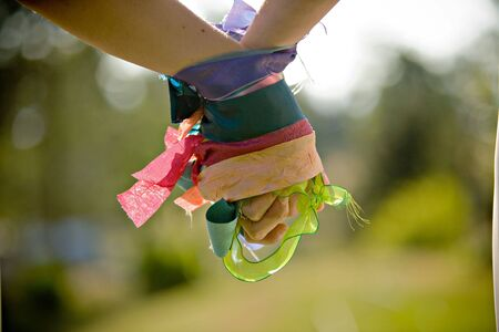 A pair of female hands wrapped with colorful ribbons holding to each other Stock Photo