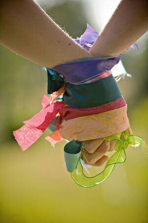 A pair of female hands wrapped with colorful ribbons holding to each other Banque d'images