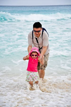 A father and his daughter playing waves at a tropical beach Stock Photo - 5567773