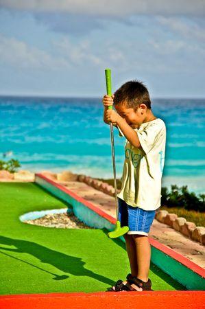 Een jongen viert zijn golf score