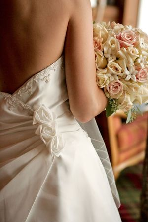 details: A back view of a bride with her bouquet Stock Photo