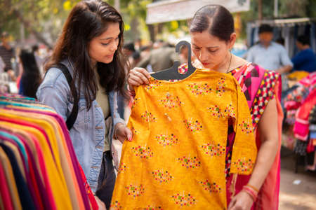 Happy mother and daughter looking and buying clothes together from outdoor street market of Delhi, India at day time.