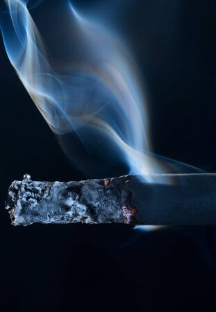 Smoldering black cigarette on black