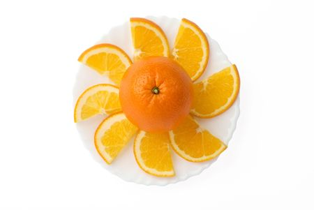 Orange fruit surrounded by orange slices on plate isolated on white background Stock Photo