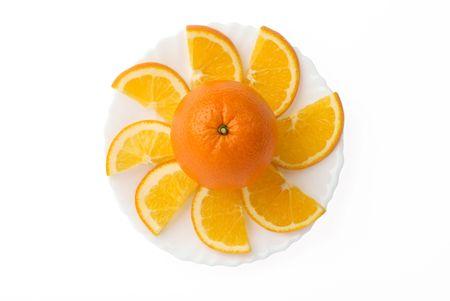 Orange fruit surrounded by orange slices on plate isolated on white background Stock Photo