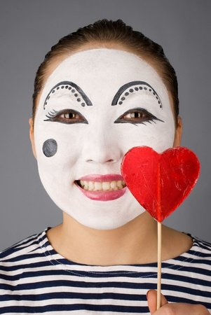 Smiling mime with the heart formed lollipop looking to the camera Stock Photo
