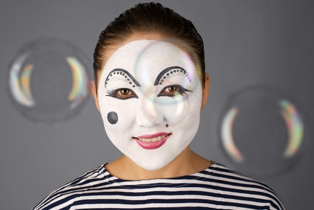 Asian mime looking to the camera trough the bubbles