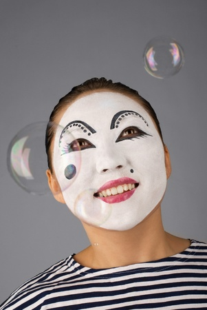 Smiling mime portrait with bubbles on grey background