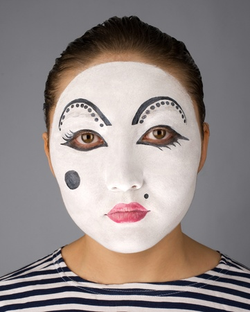 East mime on grey background looking to the camera