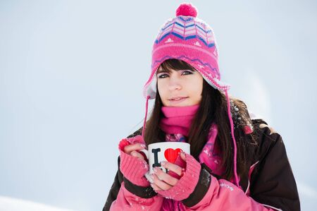 Attractive winter woman with the cup of tea on snow background Stock Photo