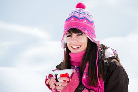 Smiling winter lady with the cup of tea on snow background