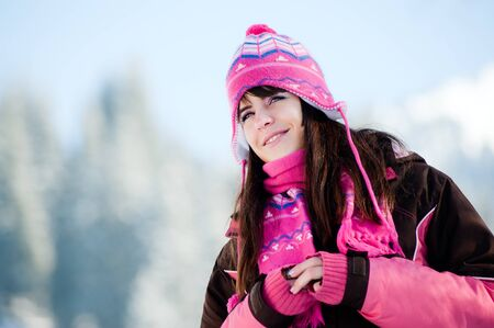 Attractive winter woman on sky and mountains background Stock Photo