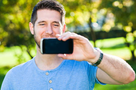 Young man in park with smart phone photo