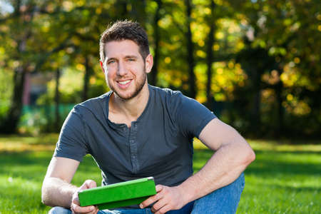 Young man in park with tablet photo