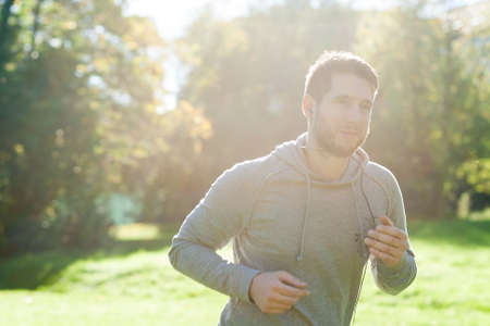 Young man in park running photo