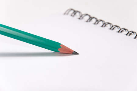 sharp pencil: Green graphite sharp pencil writing on white paper, notebook, close-up