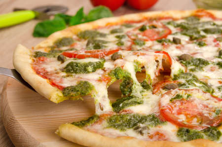 Pizza Pesto with tomatoes and capers, a slice of pizza with cheese stretching, close-up Stock Photo - 56602450
