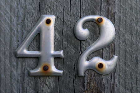 Metal Number 42 Nailed to Weathered Wood Post