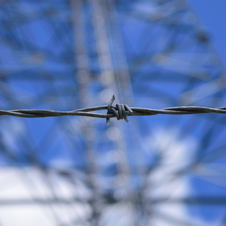 barrier: Closeup of Barbed Wire with Tower Stock Photo