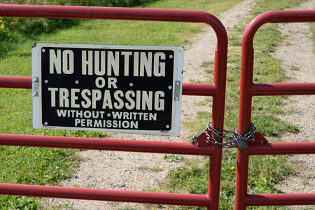 No Hunting or Trespassing Sign on Locked Gate