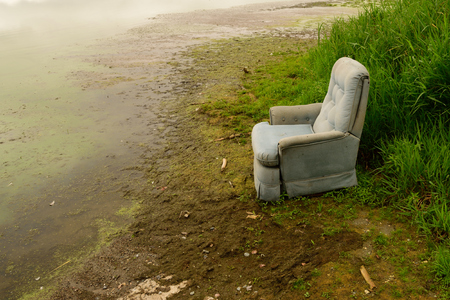 swampy: Old Recliner Sitting on Shore of Swampy Lake Stock Photo