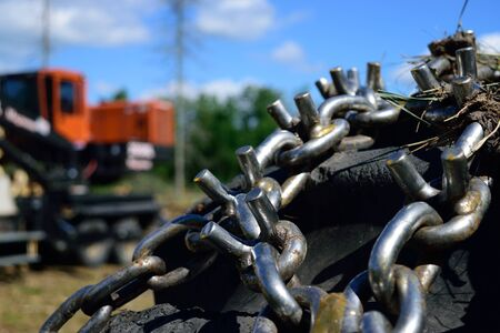 Skidder Tire with Loader in Background Stock Photo