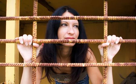 enslaved: Young woman looks afar, from behind a rusty lattice Stock Photo