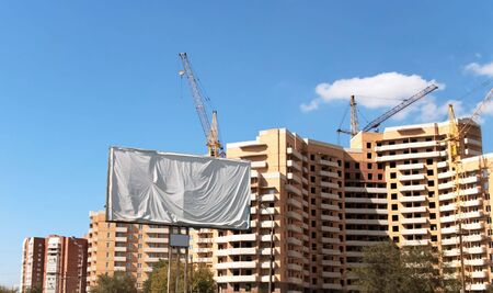 Publicity board is closed by a white material on a background of new under construction buildings photo