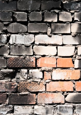 Grunge background from burnt roughly brick wall photo