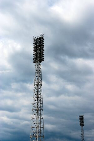 Stadium light towers against a setting sky photo