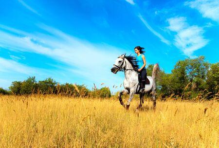 Preciosa niña montar un caballo sobre naturaleza