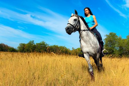 Beautiful girl riding a horse on nature photo