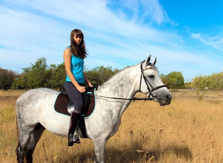 Beautiful girl riding a horse on nature. Selective focus this image Stock Photo - 7903917