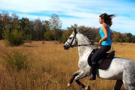 Beautiful girl riding a horse on nature. Selective focus this image photo
