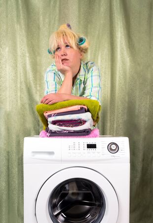 Housewife in hair curlers beside with a washing machine and pure the washed clothes Stock Photo - 8567642