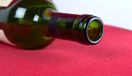 Open a bottle of wine closeup is on red background photo