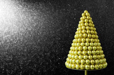 Greeting card with Christmas  Sweet xmas tree of round candies in foil on a black background covered with snow Stock Photo - 14663023