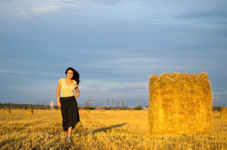 Young women goes on a field in rural areas with a bag photo