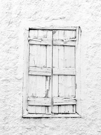 Black and white background of weathered wooden window into stone wall photo