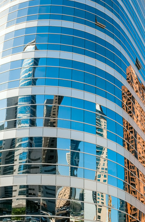 Dubai,  UAE, December, 10, 2013.  Abstract background texture with buildings reflected in windows of modern office building photo
