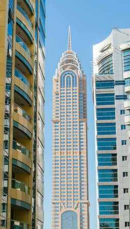 famous building:  Famous building in Dubai between two skyscrapers against blue sky