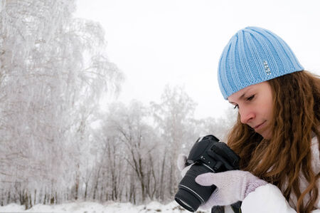 cold weather: Beautiful girl making photos outdoor in winter Stock Photo