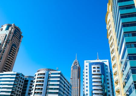 Dubai, United Arab Emirates, Modern skyscrapers against blue sky photo