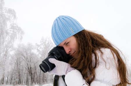 winter photos: Beautiful girl making photos outdoor in winter Stock Photo